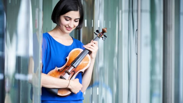 Photo of Savitri Grier holding her violin
